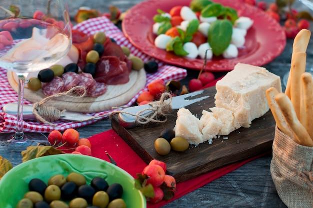 Piquenique italiano com vinho tinto, parmesão, presunto, salada caprese e azeitonas. almoço ao ar livre e mesa de madeira. petiscos tradicionais. copie o espaço