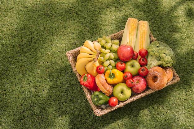 Piquenique na grama. toalha de mesa xadrez vermelha, cesta, alimentos saudáveis e frutas, suco de laranja. vista do topo. tempo de descanso de verão. postura plana.