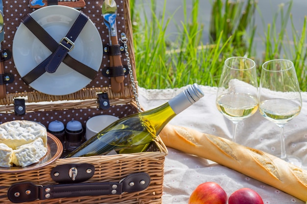 Piquenique no lago: toalha de mesa, cesta de piquenique com louças, baguete