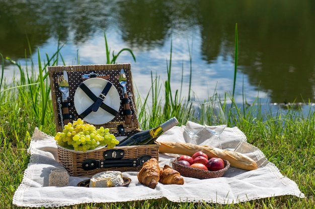 Piquenique no lago: toalha de mesa, cesta de piquenique com talheres, baguete, uvas, pêssegos