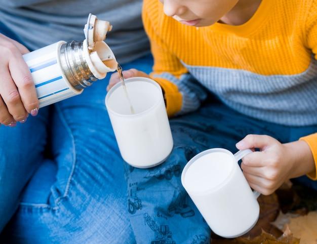 Piquenique no parque, mãos de mãe e bebê enquanto bebe chá