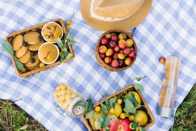 Piquenique para férias de verão com bolos frescos, frutas e bagas, dispostas em um tecido xadrez branco-azul, cesta e chapéu