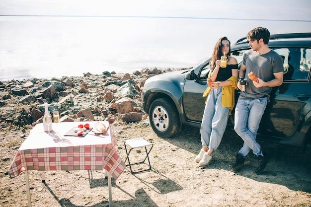 Piquenique perto da água. família feliz em uma viagem de carro. o homem e a mulher estão viajando pelo mar ou pelo oceano ou pelo rio. passeio de verão de automóvel.