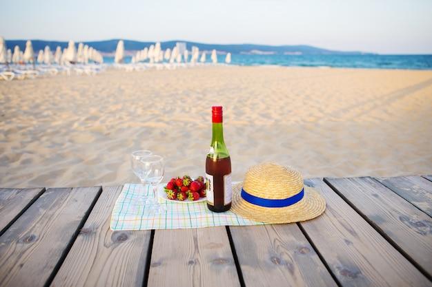 Piquenique perto do chapéu do mar, vinho, copos, morango