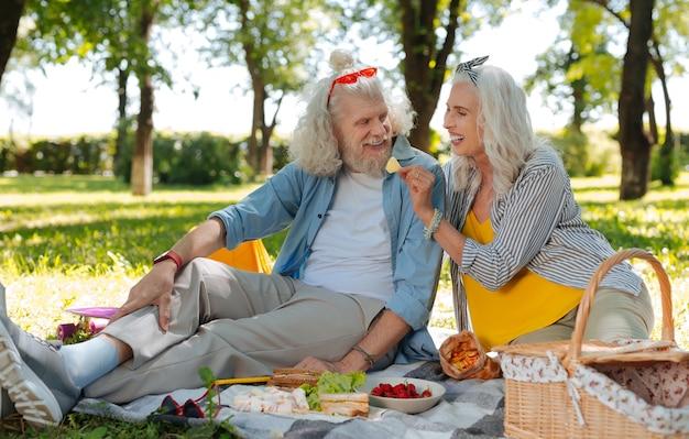 Piquenique romântico. agradável casal de idosos fazendo um piquenique romântico enquanto tem um encontro