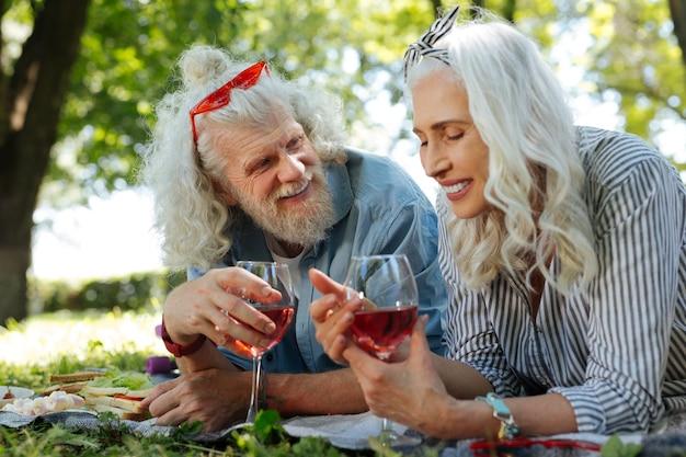 Piquenique romântico. mulher simpática e positiva segurando uma taça de vinho enquanto faz um piquenique com o marido