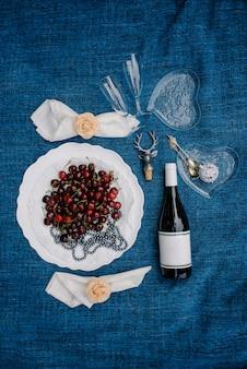 Piquenique romântico no parque em uma grama, comida deliciosa: cesta, vinho, uvas, pêssegos, baguete, cupcakes, figos, queijo, toalha de mesa azul, dois copo de vinho com champanhe
