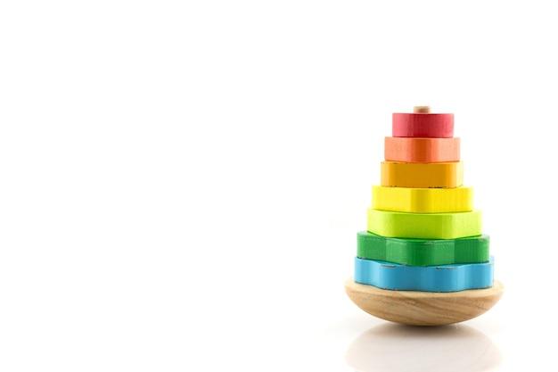 Pirâmide construída com anéis de madeira coloridos. brinquedo para bebês e crianças aprenderem com alegria habilidades mecânicas e cores. isolado em um fundo branco.