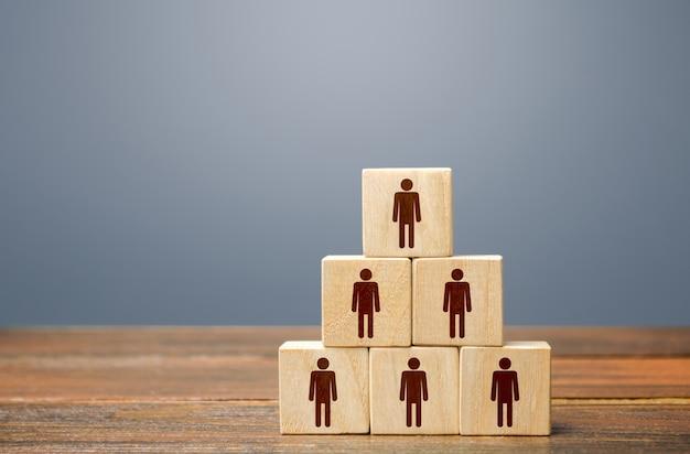 Pirâmide de blocos com pessoas. esforços conjuntos para atingir a meta. trabalho em equipe, cooperação e colaboração