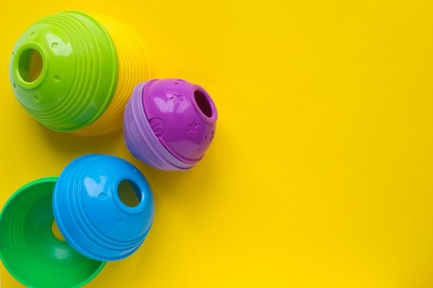 Pirâmide de brinquedo infantil colorido. brinquedos para o desenvolvimento da primeira infância em fundo amarelo. copyspace