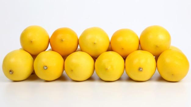 Pirâmide de limões inteiros em um fundo branco. vitamina e comida saudavel