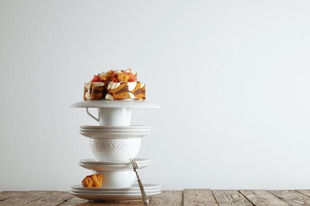 Pirâmide de lindas xícaras e pires de porcelana branca com um bolo de casamento não tradicional no topo