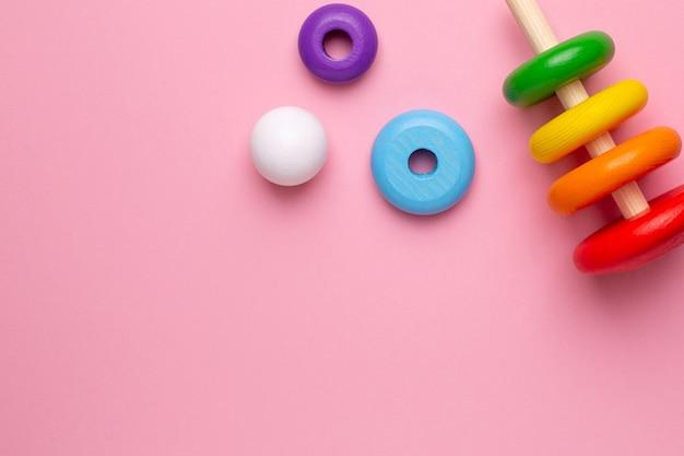 Pirâmide de madeira infantil colorida em um fundo rosa, vista superior do brinquedo para crianças e bebês