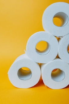 Pirâmide de papel higiênico em fundo laranja. estoques de rolo de papel higiênico branco enquanto pandêmico.