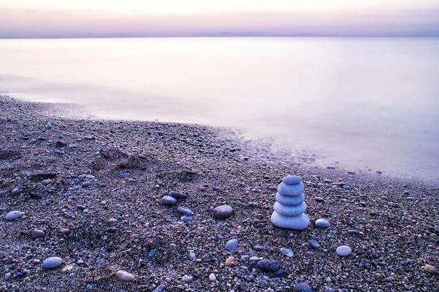 Pirâmide de pedra zen na praia ao amanhecer