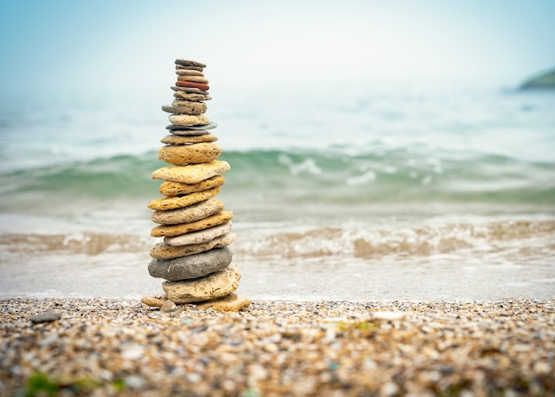 Pirâmide de pedras na areia, simbolizando o zen, harmonia, equilíbrio. energia positiva. oceano ao fundo