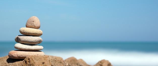 Pirâmide de pedras na costa do mar azul, harmonia, panorâmica