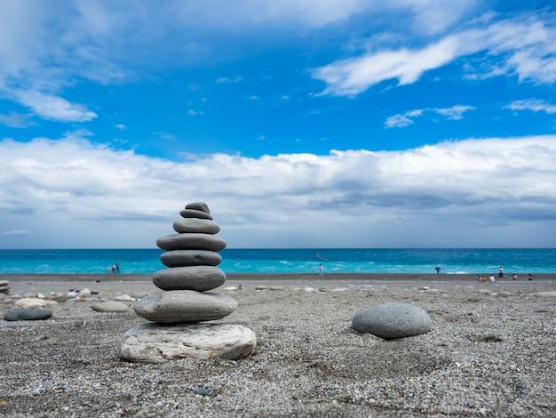 Pirâmide de seixos do mar em uma praia de areia ensolarada em hualien, taiwan.
