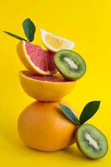 Pirâmide de toranja, kiwi e limão em equilíbrio no fundo amarelo. close-up. localização vertical.