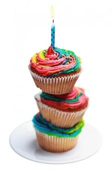 Pirâmide de três cupcakes coloridos com uma vela acesa