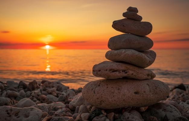 Pirâmide dos pequenos seixos na praia. pedras, no contexto da beira-mar durante o pôr do sol