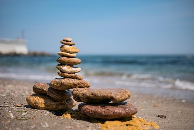 Pirâmide zen rock de pedras coloridas em uma praia de areia no fundo do mar