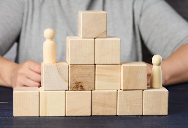 Pirâmides de cubos de madeira e estatuetas de homens na mesa. o conceito de atingir objetivos, subir na carreira. detecção de personalidade obstinada