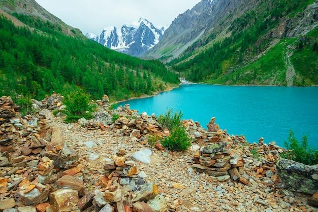 Pirâmides de pedras de equilíbrio na colina pedregosa no fundo do lago glaciar e montanha.