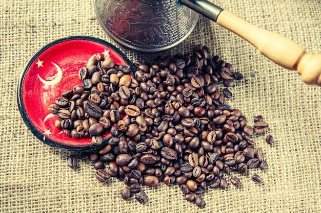 Pires com elementos da bandeira turca, grãos de café e cafeteira de cobre em pano de saco