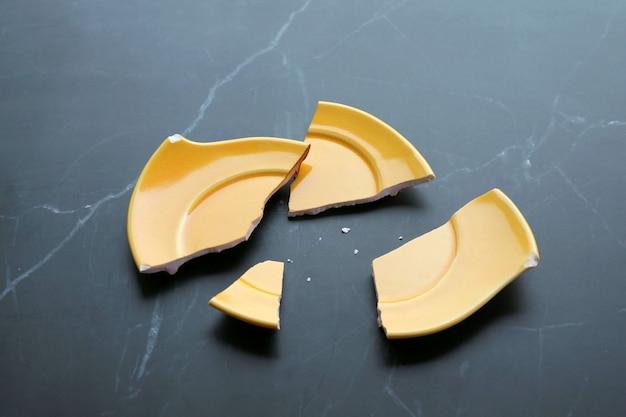 Pires de cerâmica amarela vívida quebrada espalhados na mesa de mármore preto da cozinha