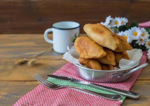 Pirojki. hambúrguer tradicional russo com batatas em uma mesa de madeira, estilo rústico, cópia espaço