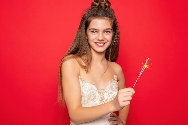 Pirotecnia e conceito de pessoas - sorrindo, jovem ou adolescente mulher feliz com estrelinhas comemorar em vestido branco sobre fundo vermelho. olhando para a câmera e sorrindo