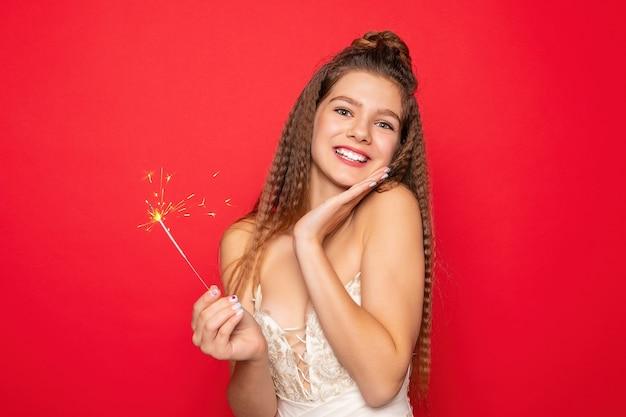 Pirotecnia e conceito de pessoas - sorrindo, jovem ou adolescente mulher feliz com estrelinhas comemorar em vestido branco sobre fundo vermelho. surpreso com sua mão e olhar para cima
