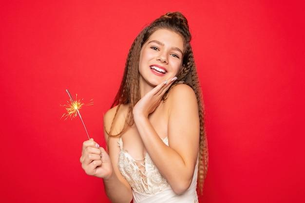 Pirotecnia e conceito de pessoas - sorrindo, jovem ou adolescente mulher feliz com estrelinhas comemorar em vestido branco sobre fundo vermelho.