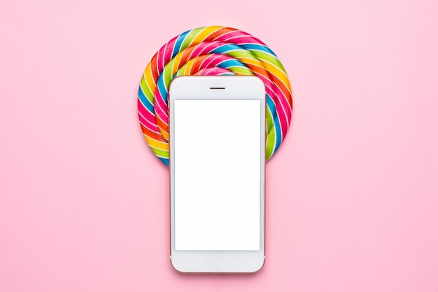 Pirulito colorido e telefone móvel em rosa