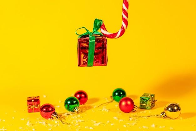 Pirulito de cana doce segurando uma caixa de presente com um presente de natal em um fundo amarelo, doces de natal com decorações de ano novo.