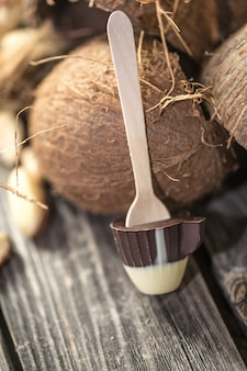 Pirulito de chocolate em forma de uma xícara pequena com coco e nozes na madeira