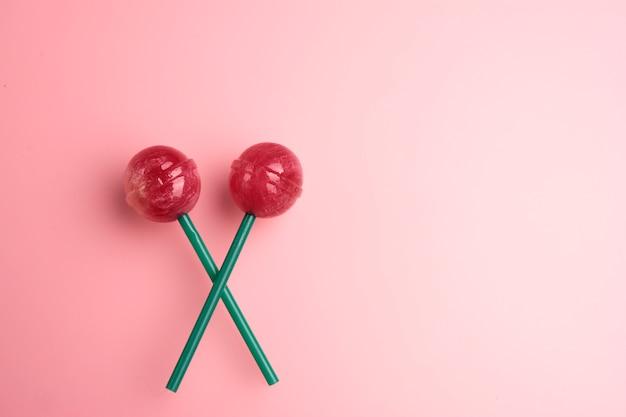 Pirulito de dois vermelhos no fundo pastel cor-de-rosa. conceito de pirulito doce. copie o espaço para o texto.
