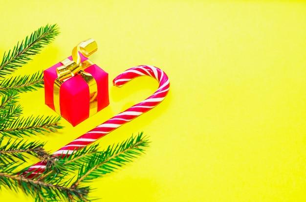 Pirulito de pirulito, presentes em fundo amarelo para o ano novo. feliz natal