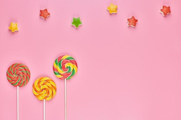 Pirulito doce e doces em fundo rosa