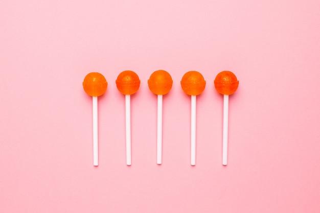 Pirulito dos doces da laranja doce no rosa pastel. composição minimalista.