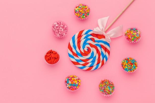 Pirulito e açúcar granulado em taças de papel no fundo rosa, vista superior