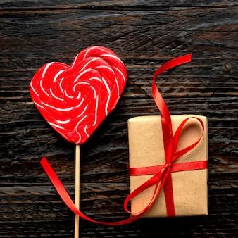 Pirulito e caixa de presente artesanal em forma de coração para o dia dos namorados em fundo de madeira escura. conceito festivo, vista superior.