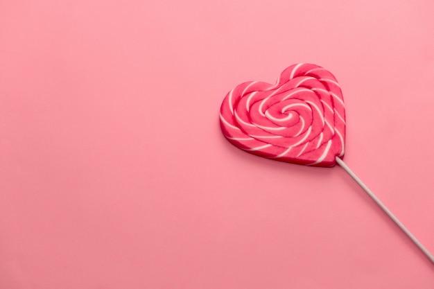 Pirulito em forma de coração doce em um rosa