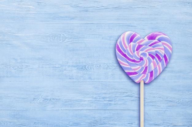 Pirulito em forma de coração listrado azul no espaço de madeira azul da cópia do fundo.