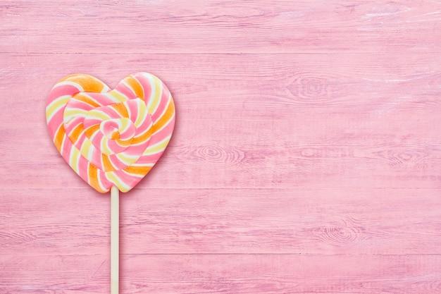Pirulito em forma de coração listrado rosa no espaço de madeira rosa da cópia do fundo.