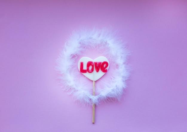 Pirulito em um coração em forma de pau em um nimbus em um espaço rosa, para texto