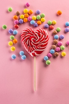 Pirulito listrado vermelho semelhante a um coração rodeado por doces coloridos doces, deitado no fundo rosa.
