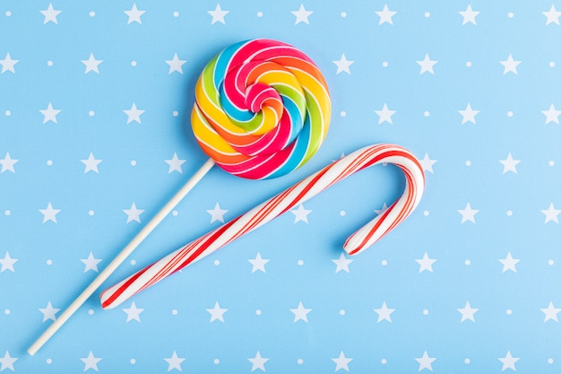 Pirulito multicolorido redondo e cone de doces isolado em um azul com fundo de estrelas. natal, inverno, ano novo ou conceito de aniversário.
