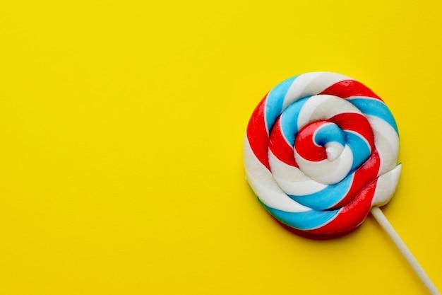 Pirulito multicolorido sobre um fundo amarelo. conceito de alimentos pouco saudáveis, açúcar, doces e doces.